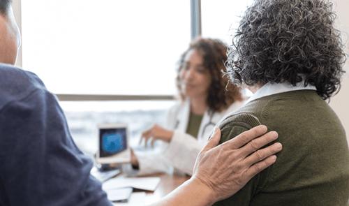 Une femme parlant avec son médecin tandis qu'un homme pose sa main sur son épaule
