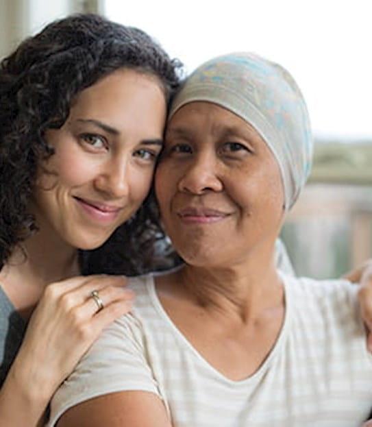 Une fille assise derrière sa mère, les mains posées sur son épaule