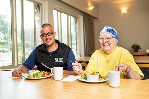 Deux invités dans une maison d'hébergement en train de manger un repas nutritif