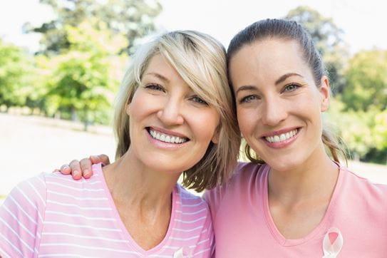 Two smiling women wearing pink shirts