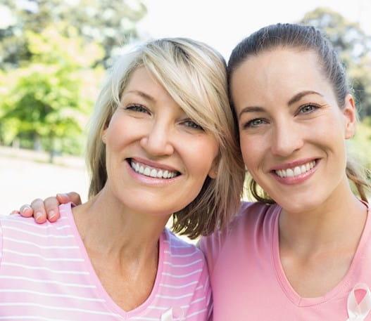 Deux femmes portant des chandails roses en train de sourire