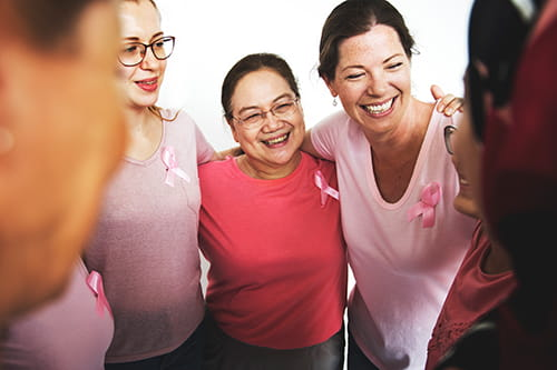A small group of women wearing pink t-shirts and a pink ribbon have their arms around each other's shoulders.