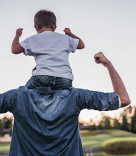 Un garçon assis sur les épaules de son père, contractant ses muscles