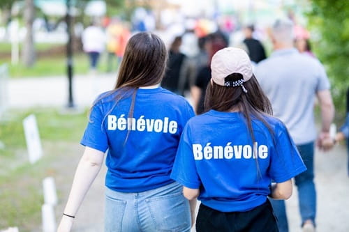 Deux jeunes femmes portent des chandails affichant le mot Bénévole à l'arrière