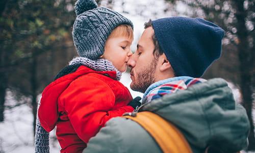 Un père tient son fils dans ses bras et leur nez se touchent