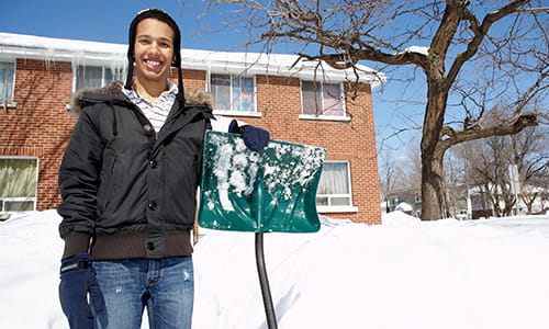 A young man is smiling and holding a snow shovel with snow behind him.