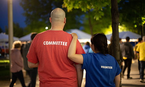 A photo of a man and a woman wearing volunteer t-shirts