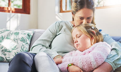 Une mère et sa fillette sont assises sur un divan. La mère embrasse le dessus de la tête de sa fille qui dort.