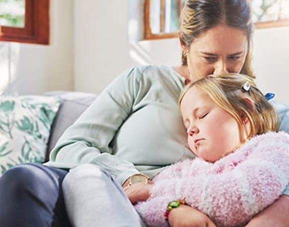 A mother and her young daughter are sitting on a couch. The mother is kissing the top of her daughter's head while her daughter sleeps.