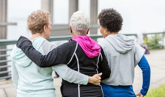 Three female friends with their arms around each other