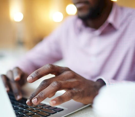 Un homme sur un ordinateur portatif faisant la recherche en ligne
