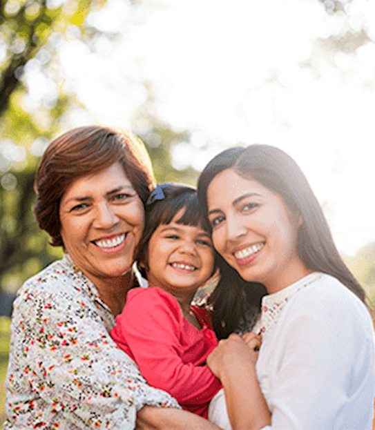A grandmother, daughter, and granddaughter hugging in a park.