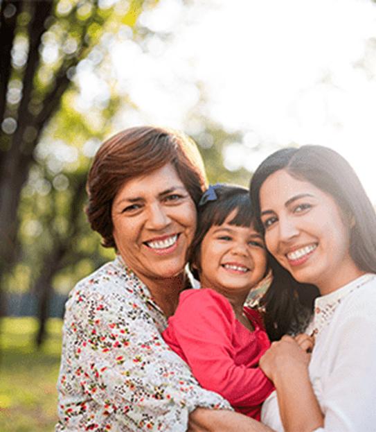 Une grand-mère, une fille et une petite-fille se serrant dans un parc.