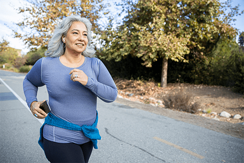 An older woman jogging down the road