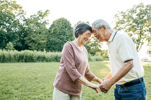An older couple facing each other and holding hands