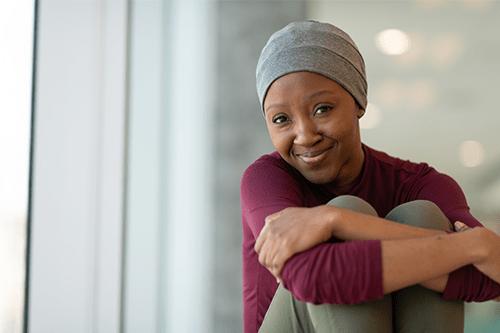 Une femme assise avec ses jambes croisées et souriant