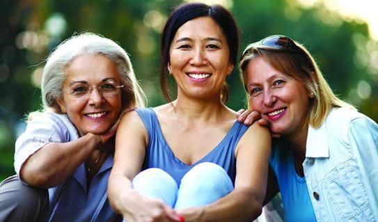 Trois amis féminins s'asseyant ensemble et souriant