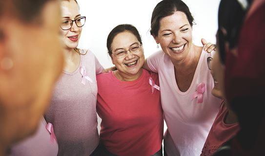 Un groupe de femmes utilisant le rose avec les bras autour de l'épaule de l'un l'autre