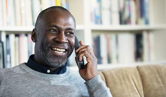 Un homme souriant tandis qu'au téléphone