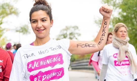 Une jeune femme portant le t shirt de la Course à la vie CIBC avec le poing dans les airs