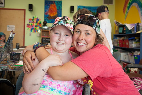 A camp counsellor with her arms wrapped around a child at summer camp