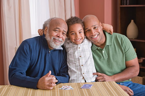 Un jeune garçon assis entre son grand-père et son père, et tous sourient