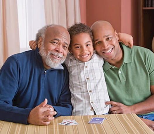 Un jeune garçon souriant et assis entre son père et son grand-père