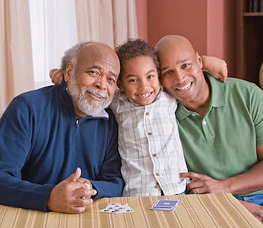 A young boy sitting between his grandfather and father. All three are smiling.