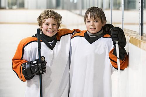 Deux jeunes joueurs de hockey souriant et s'étreignant
