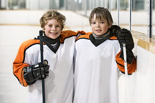 Two young male hockey players smiling with their arms around each other.