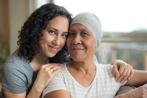 Une fille assise derrière sa mère, les bras posés sur ses épaules
