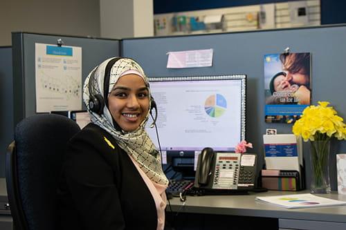 Une spécialiste de l'information sur le cancer avec un casque et assise à son bureau