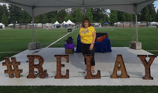 Lianne Wilson standing behind a sign that says Relay