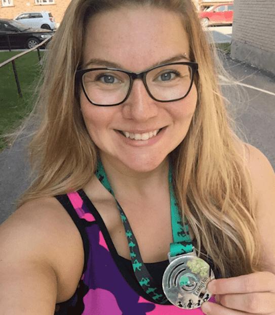 Karine souriante et tenant une médaille