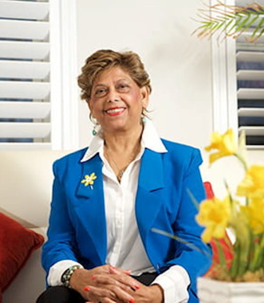 Yaslyma wearing a daffodil pin and sitting next to a bouquet of daffodils