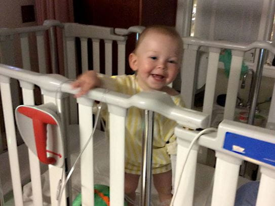 Aeson smiling while standing in his hospital bed