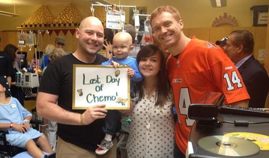 Aeson and his parents celebrates his last day of chemotherapy with Canadian football quarterback, Travis Lulay.