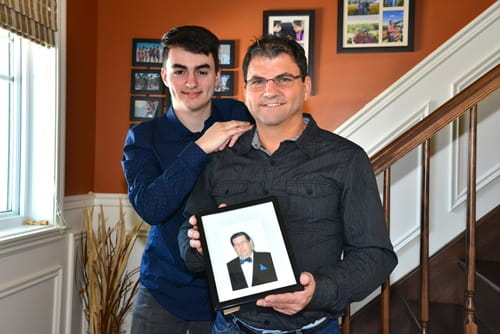 Denis Dupuis holding a photo and standing with his teenage son