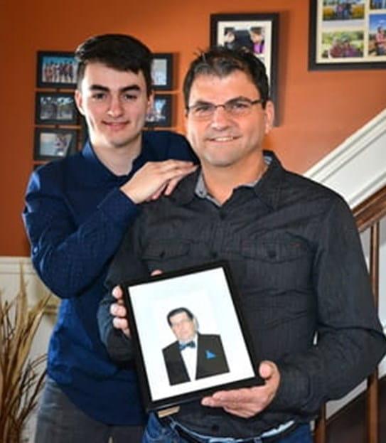 Denis Dupuis se tient debout, une photo à la main, avec son fils adolescent