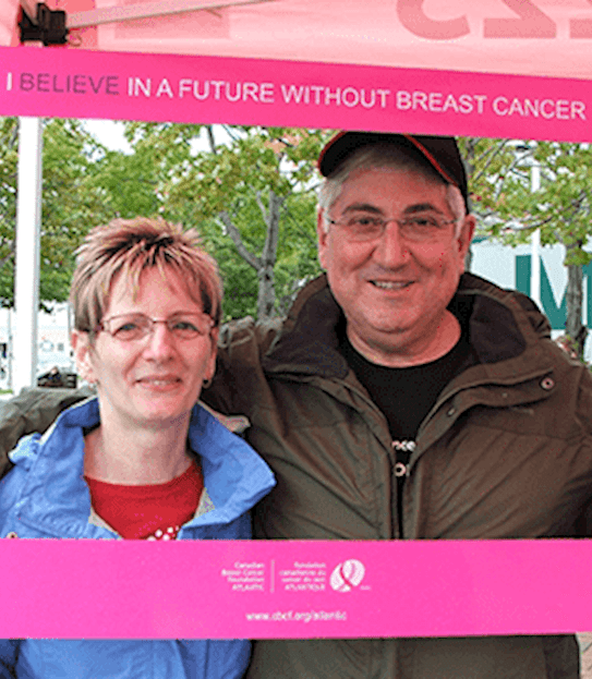 A man and woman posing while holding a pink breast cancer awareness frame.