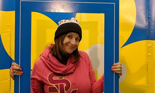 Sarah Midea, Cancer Survivor, holding up a a large sized event photo frame