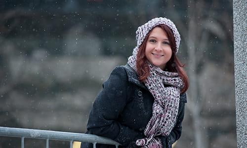 Sarah Midea, survivante de cancer, appuyée sur une rampe à l'extérieur