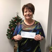 Cindy holding up a cheque of her money prize