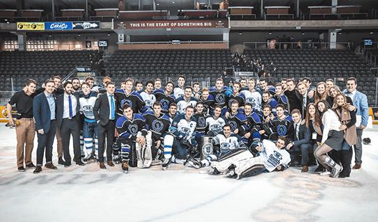 Les équipes de hockey des facultés de commerce et de génie de l'Université Queen's se tiennent sur une patinoire avec le comité organisateur de Cure Cancer Classic.