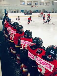Les joueurs d'une équipe de la ligue de hockey mineur se mettent en rang et regardent leurs coéquipiers jouer sur la glace.