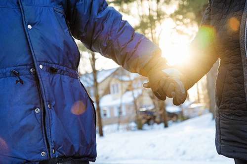 A close up of people holding hands in winter