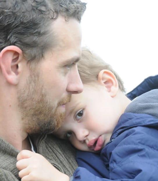 Tyler tenant son fils, dont la tête repose sur son épaule.