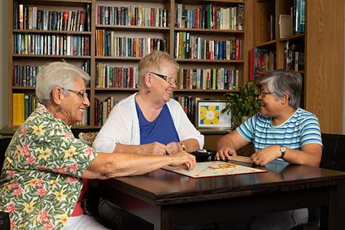 Trois dames âgées assises à une table et jouant au Scrabble.