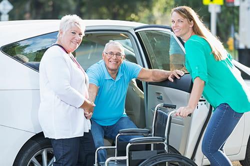 Jeune femme et dame plus âgée aidant un homme âgé à sortir de sa voiture pour l'installer dans un fauteuil roulant.