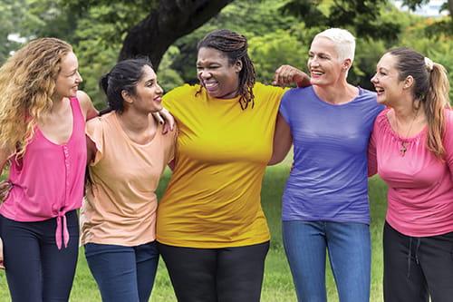 Cinq femmes regroupées, les bras posés sur les épaules les unes des autres.